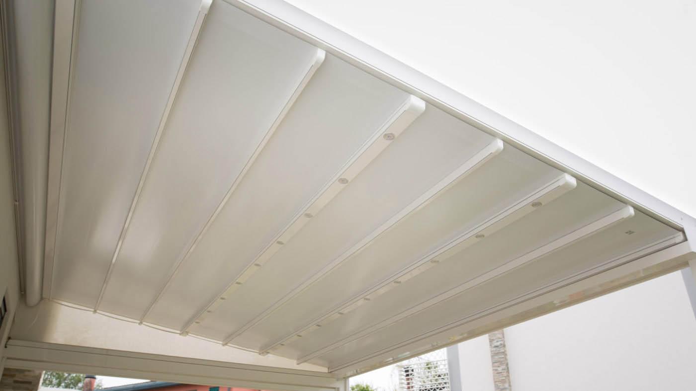 Pergola entreparedes desplegada con guías de aluminio y cubierta retráctil de lona PVC